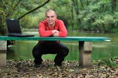 Giovane uomo d'affari in camicia rossa che lavora al computer portatile fotografia stock