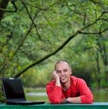 Giovane uomo d'affari in camicia rossa che lavora al computer portatile fotografie stock libere da diritti