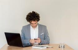 Giovane uomo d'affari caucasico che si siede al suo scrittorio e che per mezzo del suo telefono cellulare davanti al chiaro conce fotografia stock