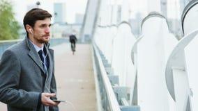 Giovane uomo d'affari che è all'aperto e frustrato durante la telefonata archivi video