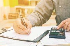 Giovane uomo d'affari che analizza le finanze con usando calcolatore e w Immagini Stock