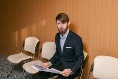 Giovane uomo d'affari che attende con il giornale Fotografie Stock Libere da Diritti
