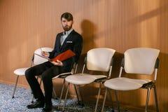 Giovane uomo d'affari che attende con il giornale Immagine Stock