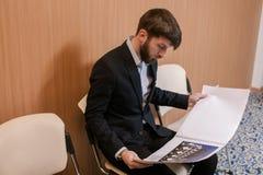 Giovane uomo d'affari che attende con il giornale Fotografia Stock