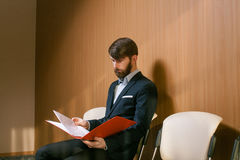 Giovane uomo d'affari che attende con il giornale Immagini Stock Libere da Diritti