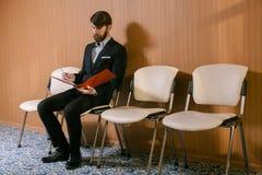 Giovane uomo d'affari che attende con il giornale Fotografia Stock Libera da Diritti