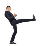 Giovane uomo d'affari che dà dei calci a qualcuno o qualcosa isolato su un fondo bianco Fotografia Stock