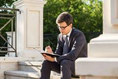 Giovane uomo d'affari che fa le note Fotografia Stock