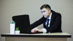Giovane uomo d'affari che gioca un gioco di computer sul lavoro Un impiegato si siede indietro mentre lavora archivi video