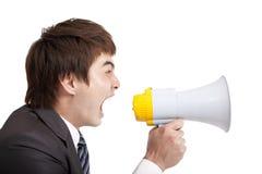Giovane uomo d'affari che grida dal megafono Fotografia Stock