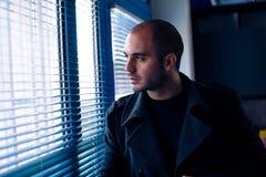 Giovane uomo d'affari che guarda attraverso la finestra in ufficio fotografie stock