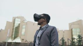 Giovane uomo d'affari che ha esperienza di VR facendo uso di una cuffia avricolare di 360 realtà virtuali all'aperto video d archivio