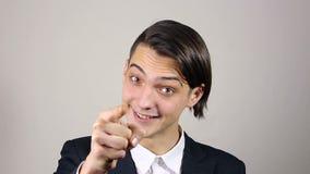 Giovane uomo d'affari che indica barretta alla macchina fotografica video d archivio