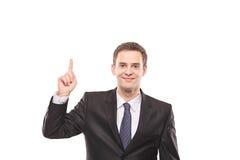 Giovane uomo d'affari che indica su con il suo dito immagine stock