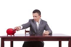 Giovane uomo d'affari che indica verso il suo porcellino salvadanaio Fotografia Stock Libera da Diritti