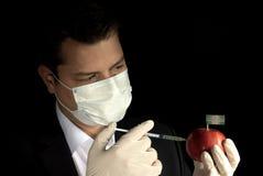 Giovane uomo d'affari che inietta i prodotti chimici in una mela con Dominic Immagini Stock Libere da Diritti