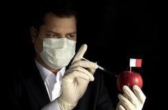 Giovane uomo d'affari che inietta i prodotti chimici in una mela con la bandiera maltese su fondo nero Immagini Stock
