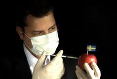 Giovane uomo d'affari che inietta i prodotti chimici in una mela con lo svedese Immagine Stock