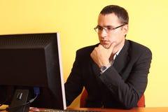 Giovane uomo d'affari che lavora al calcolatore all'ufficio Fotografia Stock