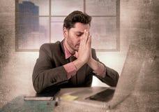 Giovane uomo d'affari che lavora al computer all'emicrania di sofferenza diminuita e triste dell'ufficio immagine stock
