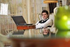 Giovane uomo d'affari che lavora al computer portatile fotografia stock