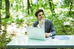 Giovane uomo d'affari che lavora al computer portatile all'aperto con la natura verde nel fondo Concetto di affari Fotografia Stock