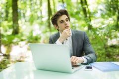 Giovane uomo d'affari che lavora al computer portatile all'aperto con la natura verde nel fondo Concetto di affari Fotografie Stock