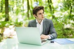 Giovane uomo d'affari che lavora al computer portatile all'aperto con la natura verde nel fondo Concetto di affari Immagine Stock Libera da Diritti