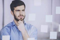 Giovane uomo d'affari che lavora al nuovo progetto con molte note appiccicose sullo schermo di vetro in ufficio Fotografia Stock