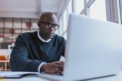 Giovane uomo d'affari che lavora al suo computer portatile Fotografia Stock Libera da Diritti