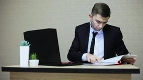 Giovane uomo d'affari che lavora all'ufficio, scrivente su un computer portatile video d archivio