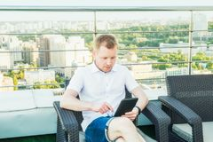 Giovane uomo d'affari che lavora alla compressa del computer portatile che si siede confortevolmente sulla sedia sul balcone del  fotografie stock libere da diritti