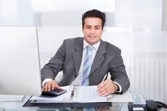 Giovane uomo d'affari che lavora allo scrittorio Fotografia Stock Libera da Diritti