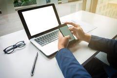 Giovane uomo d'affari che lavora con il computer portatile e lo Smart Phone sul suo DES immagini stock