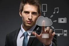 Giovane uomo d'affari che lavora con la tecnologia della nuvola fotografie stock