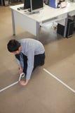 Giovane uomo d'affari che lega sul pavimento nell'ufficio Fotografia Stock