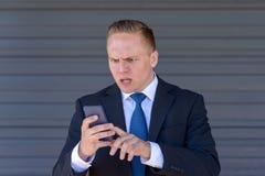 Giovane uomo d'affari che manda un sms sul suo cellulare Immagine Stock