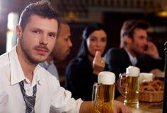 Giovane uomo d'affari che mangia birra in pub Fotografie Stock Libere da Diritti