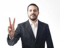 Giovane uomo d'affari che mostra il segno di pace fotografie stock