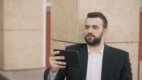Giovane uomo d'affari che parla sul computer della compressa che ha video chiacchierata con la sua moglie Uomo di affari che usan video d archivio