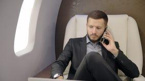 Giovane uomo d'affari che parla sul telefono, facendo uso della compressa nell'interno dell'aeroplano aereo dell'imprenditore stock footage
