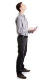 Giovane uomo d'affari che per mezzo del calcolatore del ridurre in pani Fotografia Stock