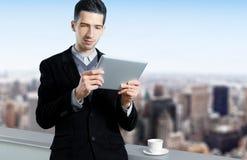 Giovane uomo d'affari che per mezzo di un calcolatore del ridurre in pani Immagini Stock
