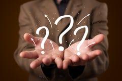 Giovane uomo d'affari che presenta i punti interrogativi disegnati a mano Immagini Stock