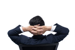 Giovane uomo d'affari che riposa sulla poltrona con le sue mani dietro il suo testa fotografia stock libera da diritti
