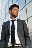 Giovane uomo d'affari che sembra costruzione moderna futura Fotografia Stock