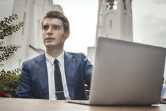 Giovane uomo d'affari che si siede al caffè della via accanto al computer portatile e che guarda da parte fotografia stock