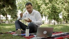 Giovane uomo d'affari che si siede nell'erba e che pranza in un'estate del parco Fotografie Stock Libere da Diritti