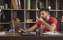 Giovane uomo d'affari che si siede nello studio con il computer portatile e sorprendente dalle notizie stupefacenti Immagini Stock