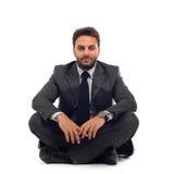 Giovane uomo d'affari che si siede sulla terra immagine stock libera da diritti